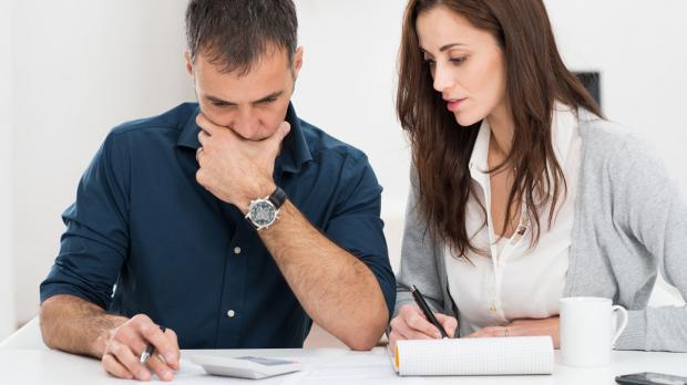 Vater und Mutter sitzen über der Haushaltsrechnung