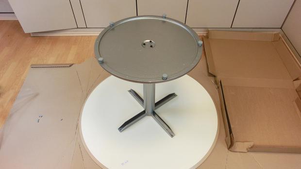 Tischgestell auf die Tischplatte stellen