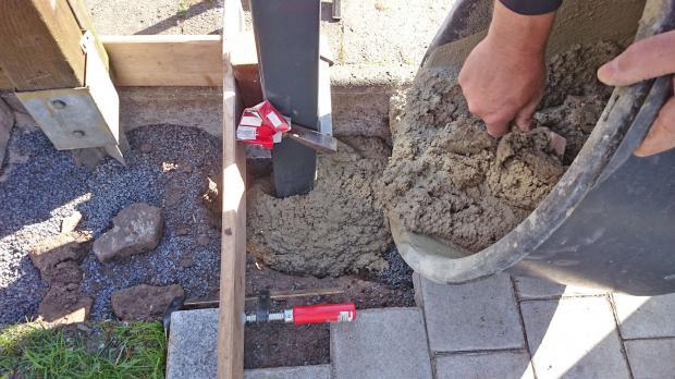 Fertigen Beton in Pfostenloch schütten