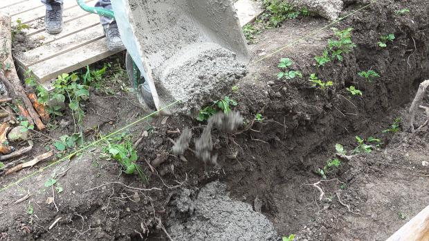 Erste Ladung Beton in den Graben füllen