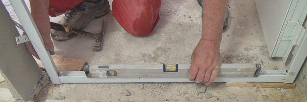 Einrichten des Rahmens der Stahlzarge bei der Dübelmontage