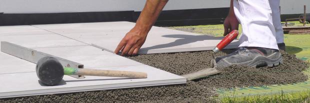 Terrassenplatte wird in den Trassdrainmörtel gelegt