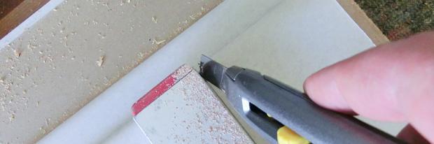 Trockenbauwerkzeuge im Überblick - Kartonschicht mit Cutter anritzen