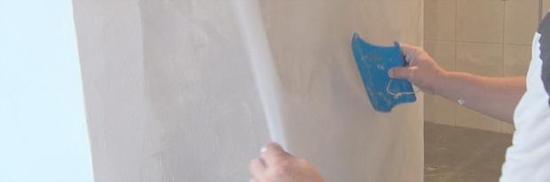 Risse im Putz ausbessern – Glasfasernetz wird mit einer Kunststoffspachtel aufgetragen