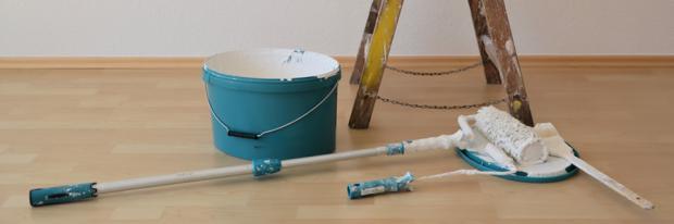 Malerwalze, Farbeimer und Leiter liegen zum Streichen bereit
